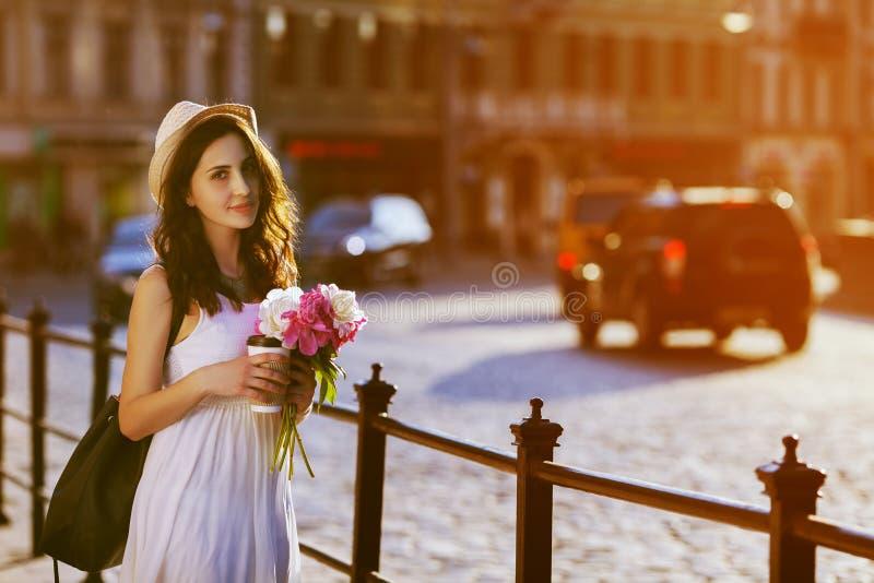 Jonge mooie dame die op straat lopen, houdend document kop met koffie en boeket van pioenen Het model modieus dragen royalty-vrije stock foto