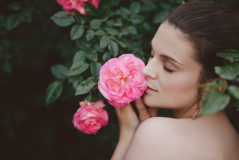 Jonge mooie dichte omhooggaand van het vrouwenportret met het perfecte huid stellen met roze rozen bloeit in een tuin royalty-vrije stock fotografie