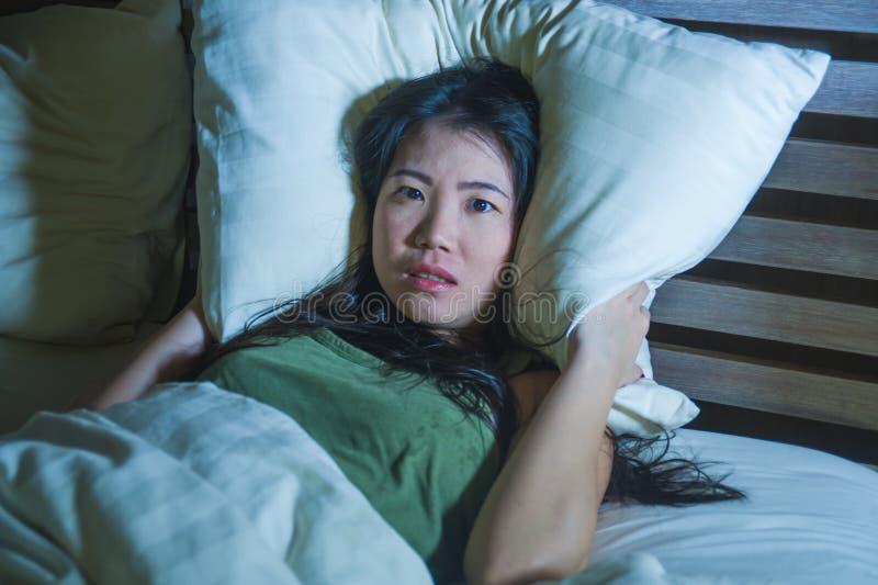 Jonge mooie doen schrikken Aziatische Chinese vrouw die wakker in bed slapeloos behandelend hoofd liggen met hoofdkussen die nach royalty-vrije stock fotografie