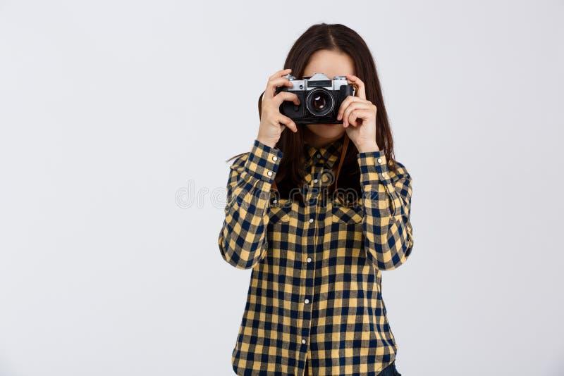 Jonge mooie donkerbruine fotograaf over witte achtergrond royalty-vrije stock fotografie