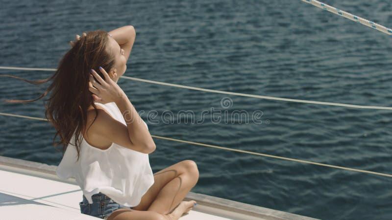 Jonge mooie donkerbruine meisjeszitting op het luxejacht stock foto
