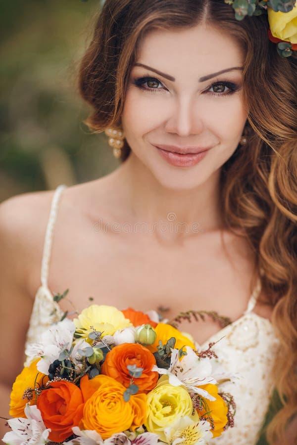 Jonge mooie donkerbruine vrouw in bloeiende tuin stock fotografie