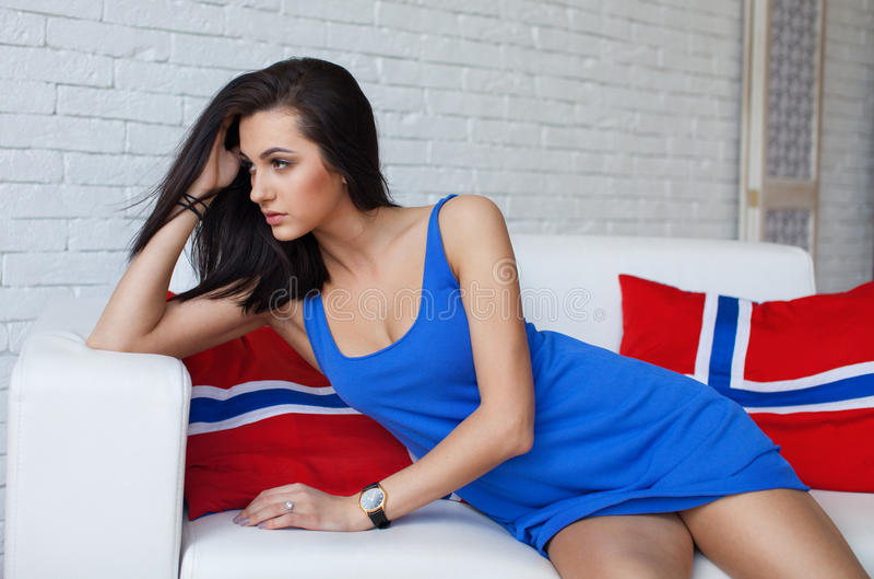 Jonge mooie donkerbruine vrouw met het lange slanke benen stellen, die modieuze kleding dragen stock foto's