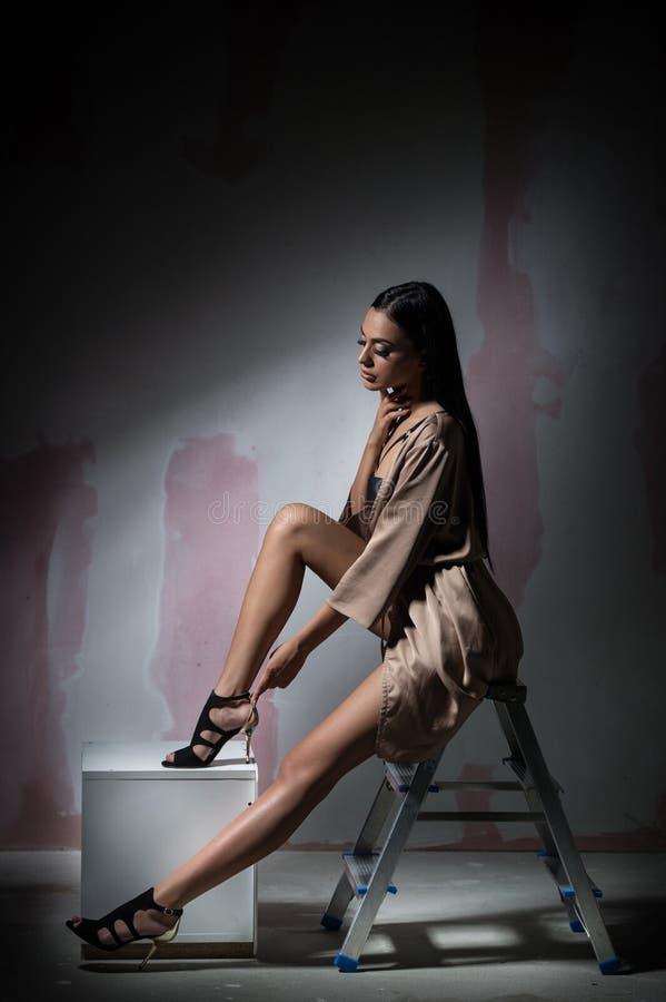 Jonge mooie donkerbruine vrouw in naakte gekleurde uitrusting, stellende manier binnen Verleidelijk donker haarmeisje met perfect royalty-vrije stock foto