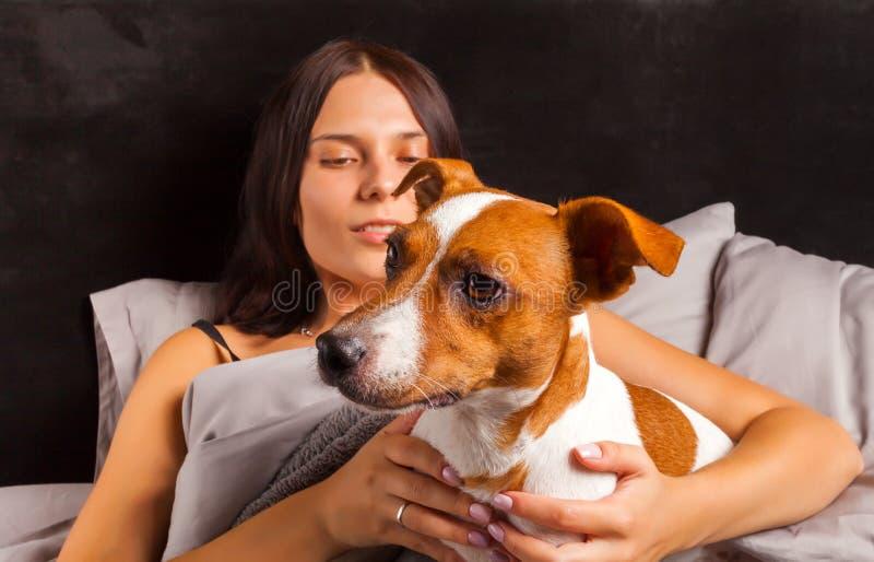 Jonge mooie donkerbruine vrouwenspelen in bed met haar hond royalty-vrije stock foto's