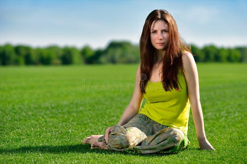Jonge mooie donkerbruine vrouwenzitting op groene weide. stock afbeeldingen