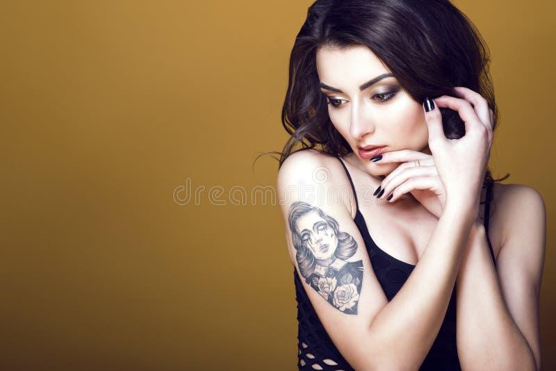 Jonge mooie donkere haired getatoeeerde vrouw die zwarte netto bovenkant dragen, haar handen houden bij haar gezicht en zorgvuldi stock foto's