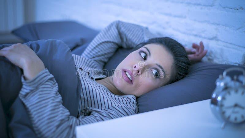 Jonge mooie droevige en ongerust gemaakte Latijnse vrouw die aan slapeloosheid lijden en wanordeprobleem onbekwaam aan slaap laat stock afbeelding