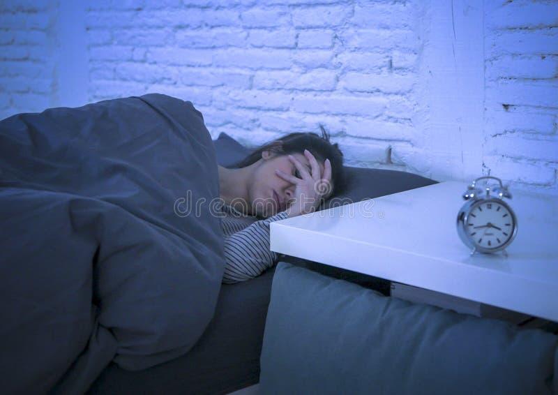 Jonge mooie droevige en ongerust gemaakte Latijnse vrouw die aan slapeloosheid lijden en wanordeprobleem onbekwaam aan slaap laat stock afbeeldingen