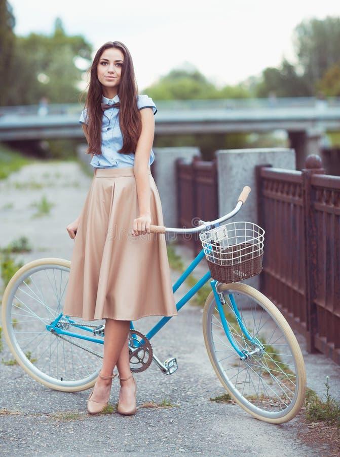 Jonge mooie, elegant geklede vrouw met fiets stock foto