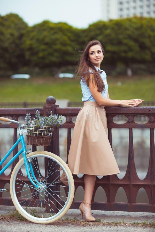 Jonge mooie, elegant geklede vrouw met fiets, de zomer royalty-vrije stock afbeelding