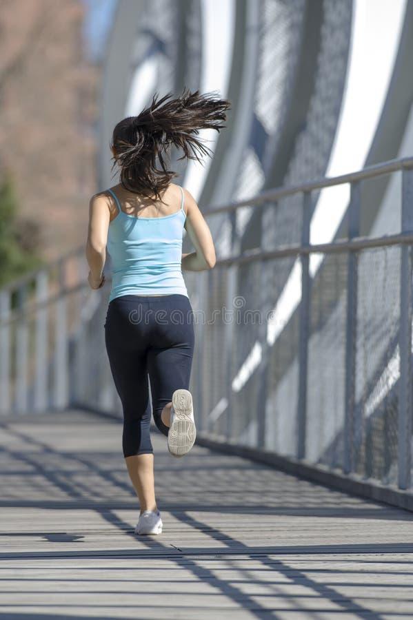 Jonge mooie en atletieksportvrouw die kruisend de moderne brug van de metaalstad lopen aanstoten royalty-vrije stock fotografie