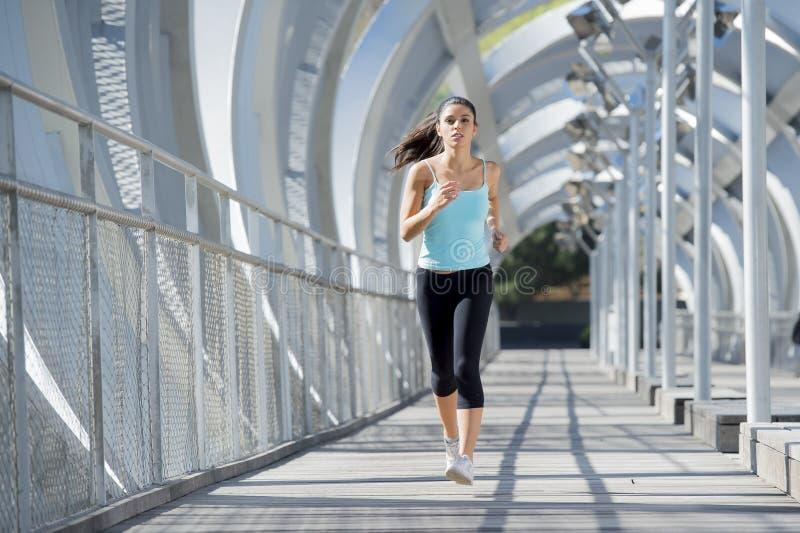 Jonge mooie en atletieksportvrouw die kruisend de moderne brug van de metaalstad lopen aanstoten stock afbeelding