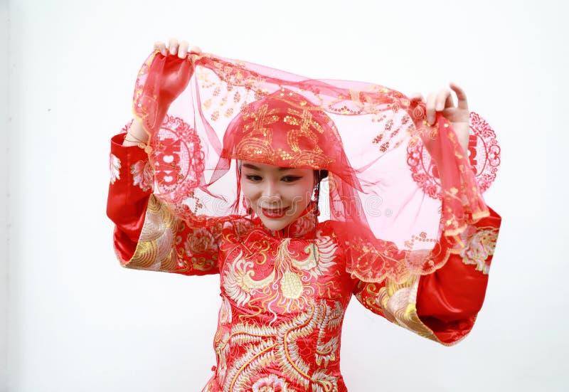 Jonge, mooie en elegante Chinese vrouw die de de zijde rode die kleding dragen van een typische Chinese bruid, met gouden Phoenix stock afbeeldingen