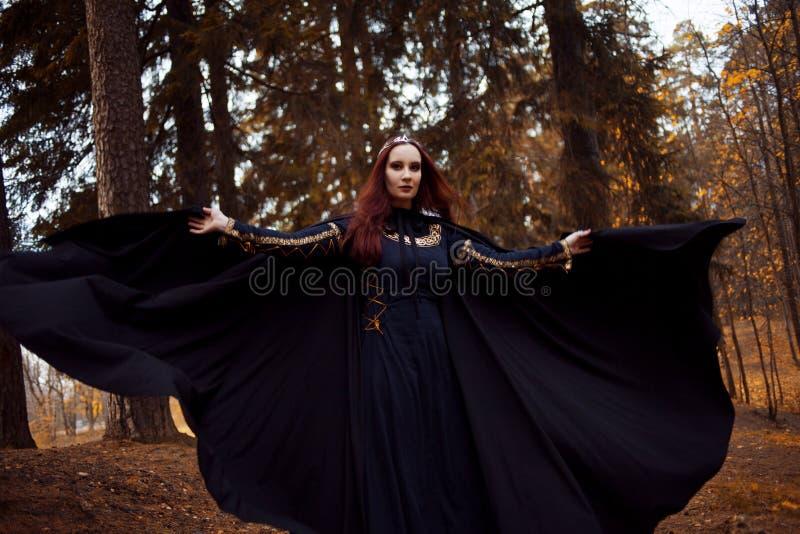Jonge mooie en geheimzinnige vrouw in hout, in zwarte mantel met kap, beeld van boself of heks stock foto