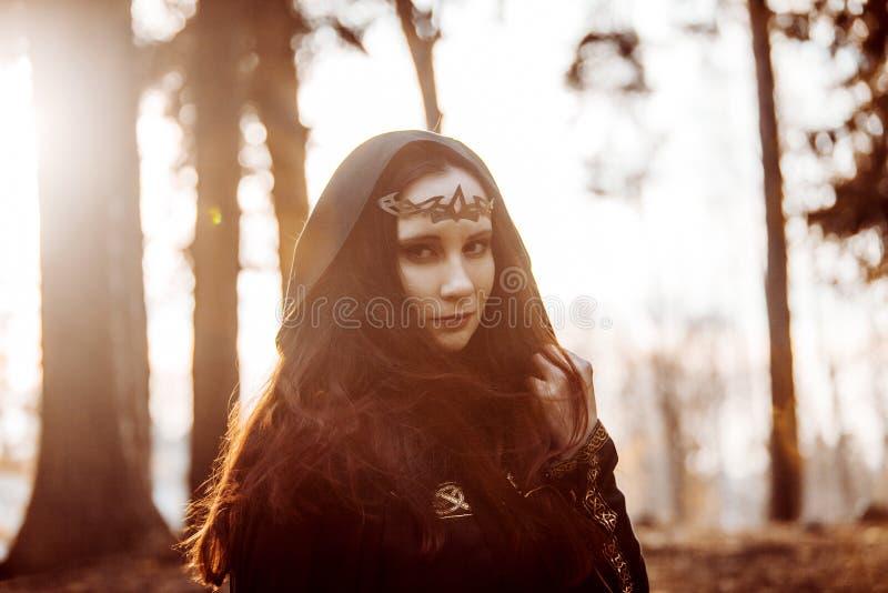 Jonge mooie en geheimzinnige vrouw in hout, in zwarte mantel met kap, beeld van boself of heks stock afbeeldingen