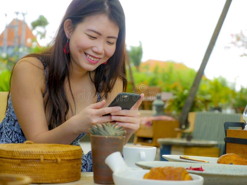 Jonge mooie en gelukkige Aziatische Chinese vrouw die de sociale media app van Internet op mobiele telefoon gebruiken die vrolijk royalty-vrije stock foto's