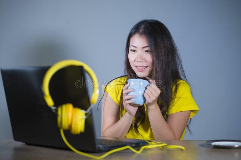Jonge mooie en gelukkige Aziatische Koreaanse vrouw die bij bureau van Internet bij laptop computer vrolijk glimlachen genieten h stock foto's