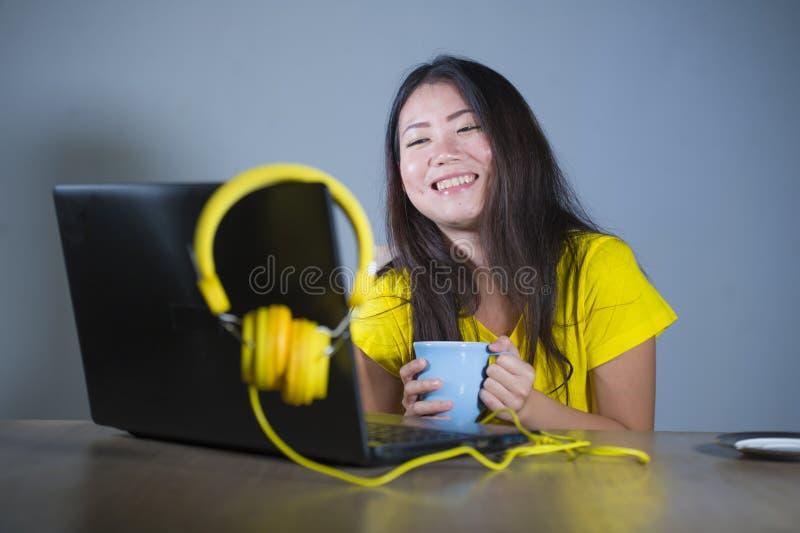 Jonge mooie en gelukkige Aziatische Koreaanse vrouw die bij bureau van Internet bij laptop computer vrolijk glimlachen genieten h royalty-vrije stock foto