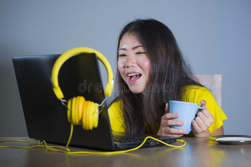 Jonge mooie en gelukkige Aziatische Koreaanse vrouw die bij bureau van Internet bij laptop computer vrolijk glimlachen genieten h royalty-vrije stock afbeeldingen