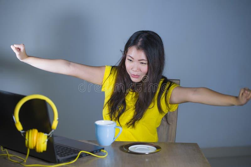 Jonge mooie en gelukkige Aziatische Koreaanse vrouw die bij bureau van Internet bij laptop computer vrolijk glimlachen genieten h royalty-vrije stock afbeelding