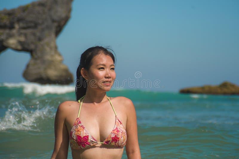 Jonge mooie en gelukkige Aziatische Koreaanse vrouw die pret glimlachen hebben ontspannen en vrolijk in het overzees die de Zomer royalty-vrije stock foto