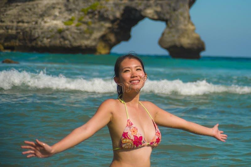 Jonge mooie en gelukkige Aziatische Koreaanse vrouw die pret glimlachen hebben ontspannen en vrolijk in het overzees die de Zomer royalty-vrije stock foto's