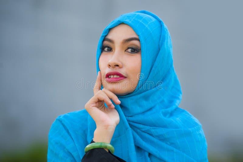 Jonge mooie en gelukkige Aziatische vrouw in hijab het moslim hoofdsjaal stellen aan de speelse camera hebbend pret en kijkend ve stock fotografie