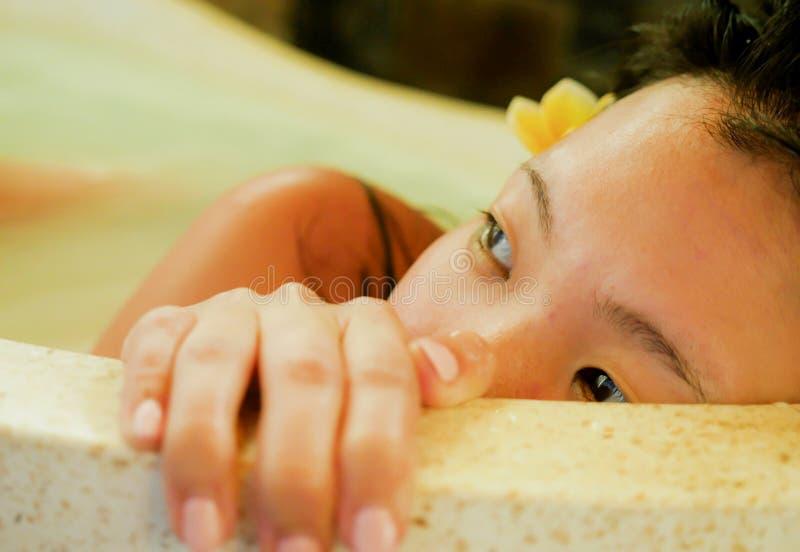 Jonge mooie en gelukkige ontspannen Aziatische Chinese vrouw die tevreden stellend melkbad in badkuip bij luxury Spa verrukt glim stock afbeeldingen