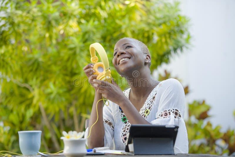 Jonge mooie en gelukkige zwarte Afrikaanse Amerikaanse vrouw die in openlucht van bij koffie genieten die met digitale tablet wer stock fotografie