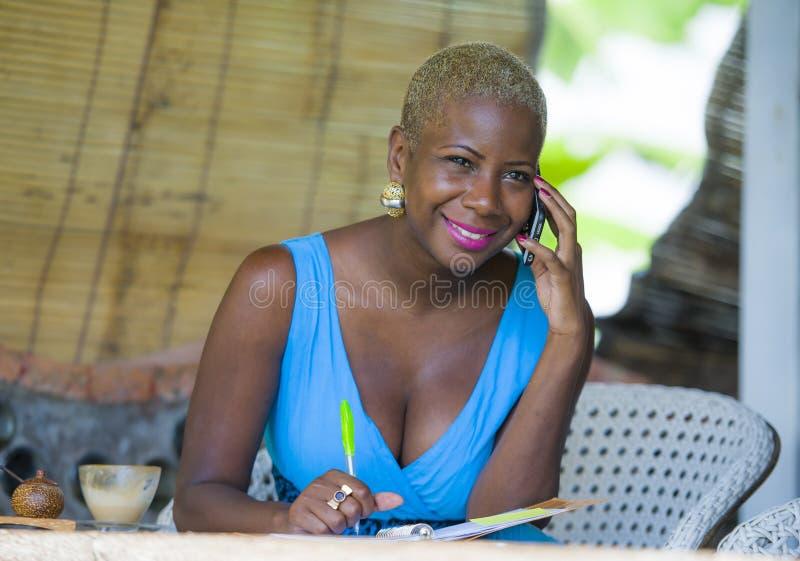 Jonge mooie en gelukkige zwarte afro Amerikaanse bedrijfsvrouw in in en modieus haar die van stadskoffie gelukkig spreken aan mo  stock afbeeldingen