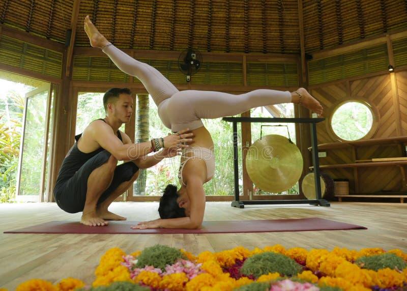 Jonge mooie en geschikte vrouw met de acrobaatmens als yogabus het leren saldohouding in acroyogatraining bij exotische geschikth stock fotografie