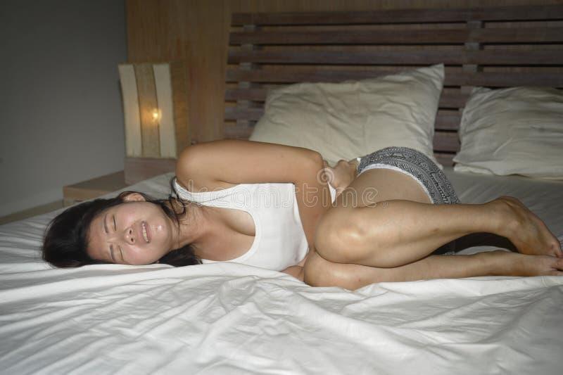 Jonge mooie en vrij Aziatische Chinese vrouw die op bed liggen die zieke en onwel lijdende buik en maagklem voelen en menstruat royalty-vrije stock afbeeldingen