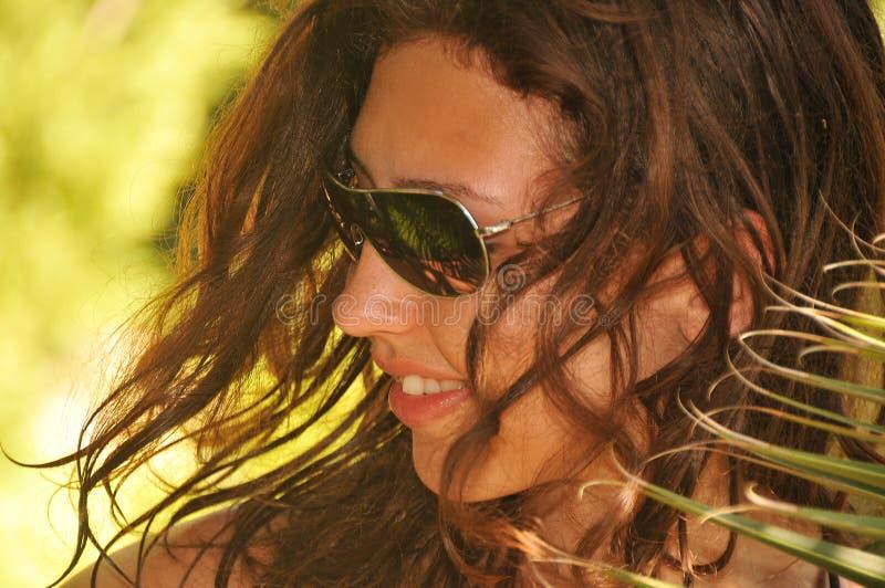 Jonge mooie gelooide vrouw die zonnebril dragen die met palm in portret bij zonnige dag stellen stock afbeeldingen