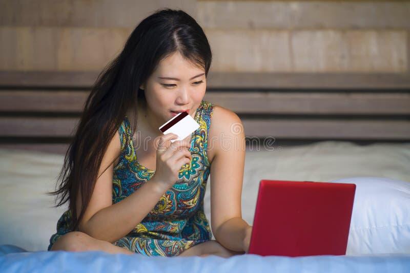Jonge mooie gelukkige Aziatische Amerikaanse vrouw die het bankwezen van creditcardinternet op laptop computer thuis in bed het w stock afbeelding