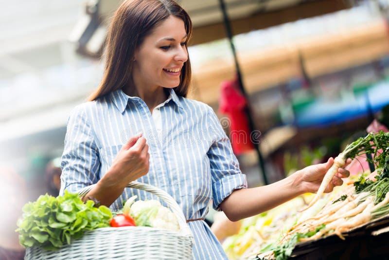 Jonge mooie gelukkige vrouw die verse groenten kopen stock fotografie