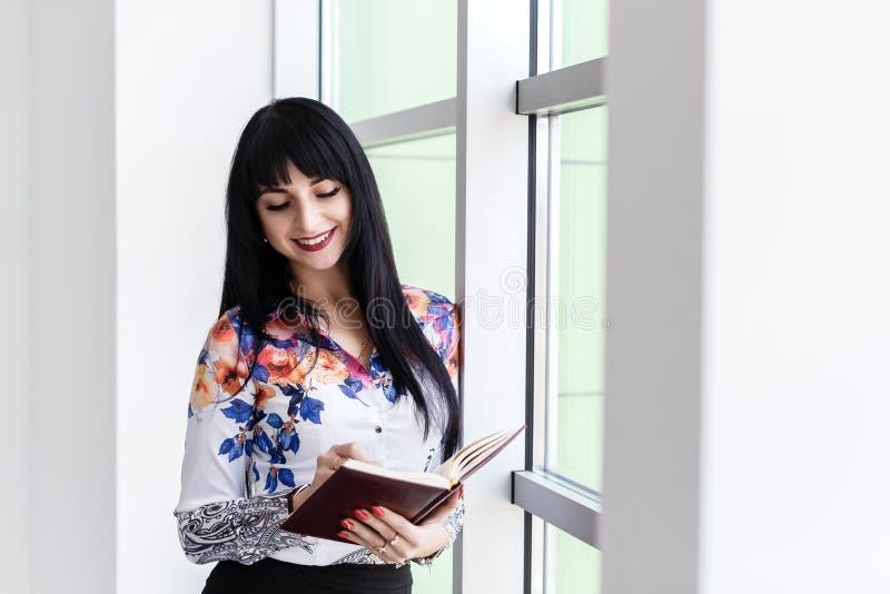 Jonge Mooie gelukkige vrouw die zich dichtbij het venster bevinden, schrijvend in notitieboekje, kijkend aan het notitieboekje, h stock foto's