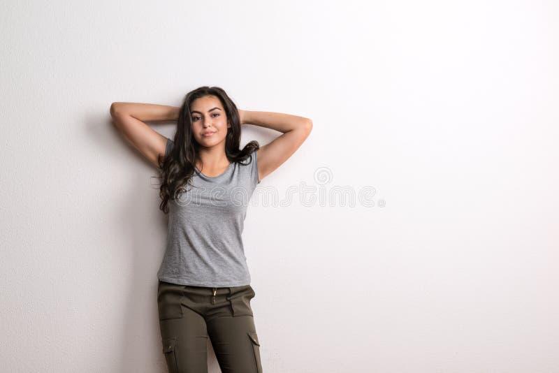 Jonge mooie gelukkige vrouw die zich in een studio in studio, handen achter haar hoofd bevinden royalty-vrije stock foto's