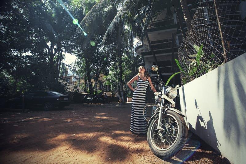Jonge mooie gelukkige vrouw met fiets op een tropische Aziatische straat stock afbeeldingen