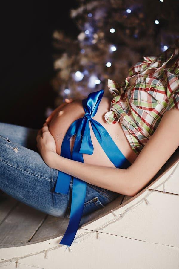 Jonge mooie gelukkige zwangere vrouw die op een achtergrond van een Kerstboom plaatsen Zwangerschap en mensenconcept royalty-vrije stock foto's