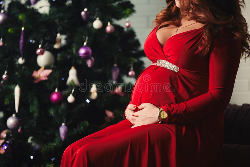 Jonge mooie gelukkige zwangere vrouw in een lange rode kleding die dichtbij nieuwe jaarboom situeren Zwangerschap en mensenconcep stock afbeelding