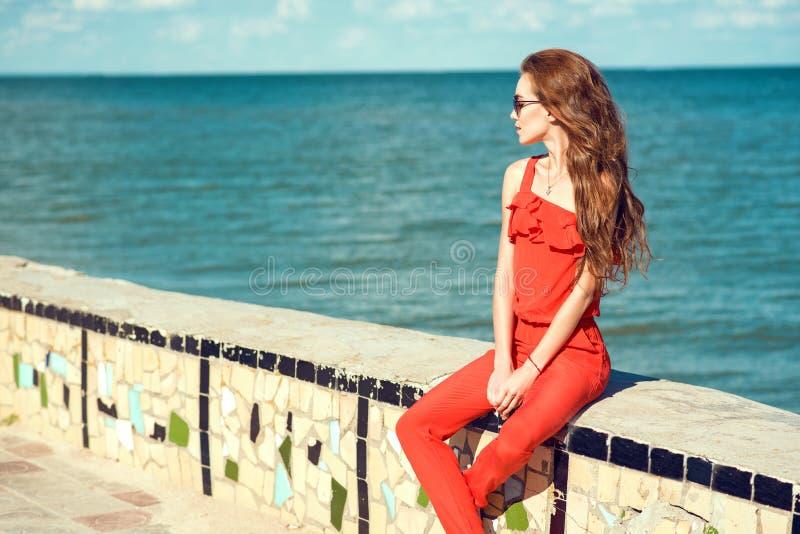 Jonge mooie glam modieuze vrouw die koraal rode jumpsuit en donkere in zonnebril dragen die op de verschansing bij de kust zitten royalty-vrije stock afbeeldingen