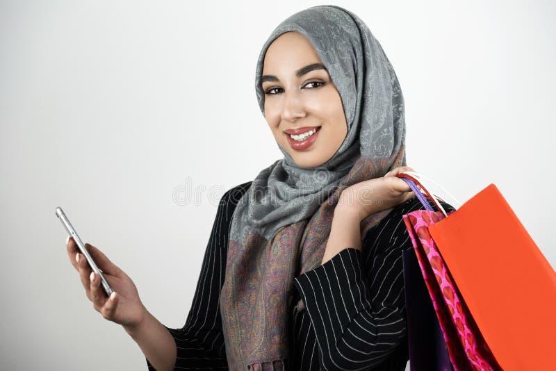 Jonge mooie glimlachende Moslim bedrijfsvrouw die smartphone van de tulband hijab headscarf holding in één hand en het winkelen d royalty-vrije stock afbeelding