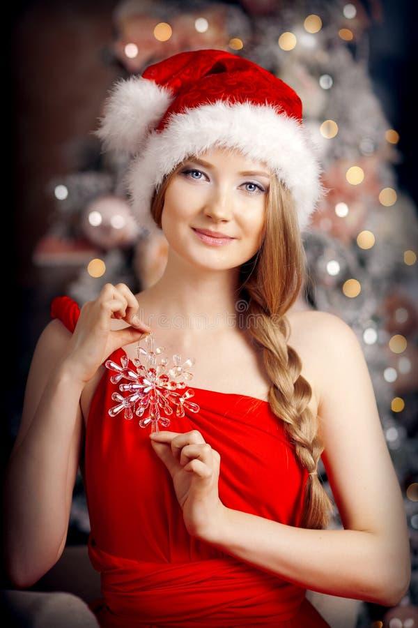 Jonge mooie glimlachende santavrouw dichtbij de Kerstboom Fas stock foto's