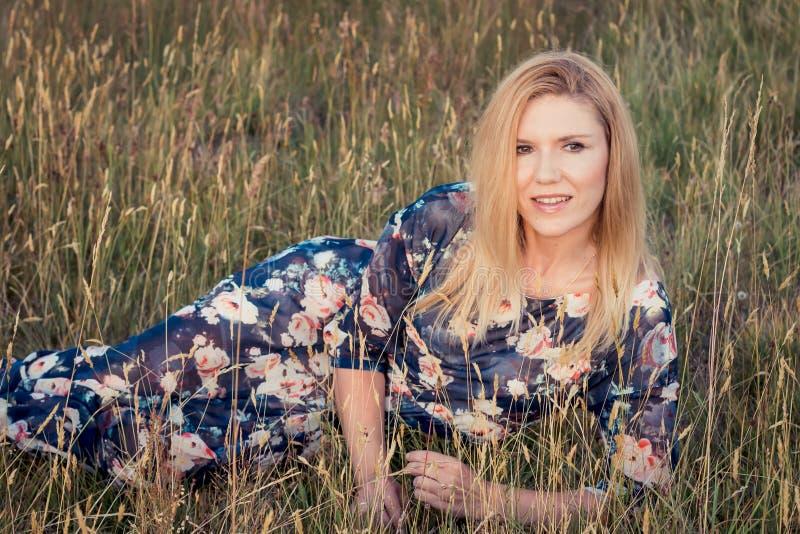 Jonge mooie glimlachende vrouw die op gras in lange avondjurk liggen royalty-vrije stock foto