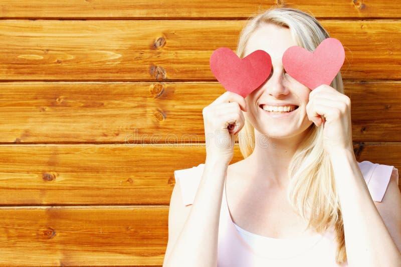 Jonge mooie glimlachende vrouw met document harten over ogen royalty-vrije stock afbeeldingen