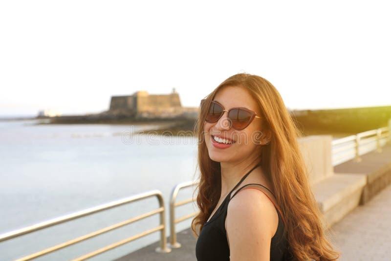 Jonge mooie glimlachende vrouw in zwart mouwloos onderhemd en zonnebril bij s stock afbeelding