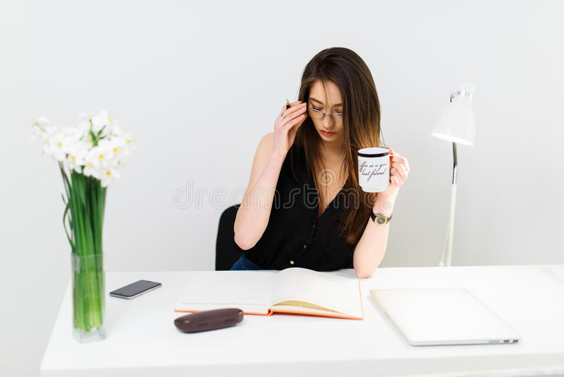 Jonge mooie het bedrijfsvrouw drinken koffie op het haar werk royalty-vrije stock afbeelding