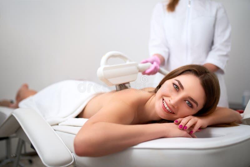Jonge mooie het glimlachen epilation van de vrouwen achterlaser in schoonheidssalon Cosmetologist die ontharingsbehandeling met e stock foto