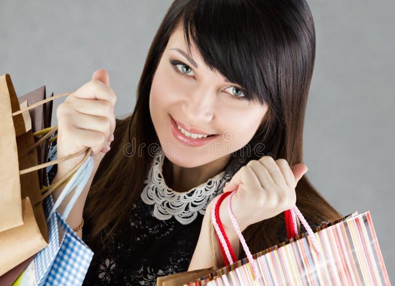 Jonge mooie het glimlachen het document van de vrouwenholding zakken royalty-vrije stock foto